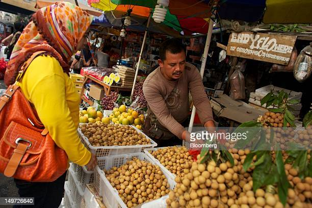 A fruit vendor selects longan for a customer at a market stall in Jakarta Indonesia on Thursday Aug 2 2012 Indonesia is expected to release...