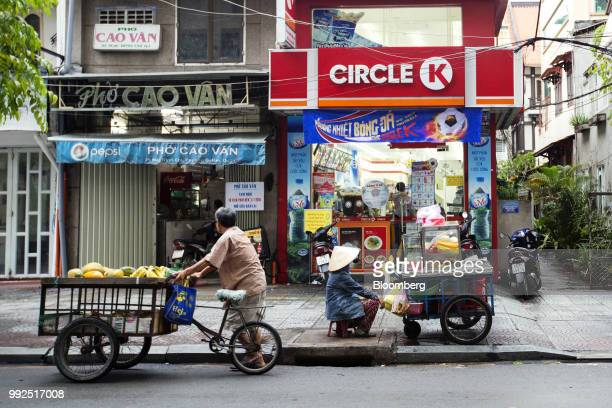 A fruit vendor sits waiting for customers at her cart as a fellow fruit vendor walks past outside a Circle K store in Ho Chi Minh City Vietnam on...
