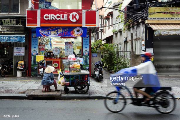 A fruit vendor sits waiting for customers at her cart outside a Circle K store in Ho Chi Minh City Vietnam on Wednesday June 20 2018 For decades...