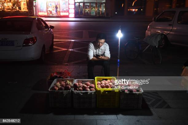 A fruit vendor waits at his stand in Dandong in China's northeast Liaoning province on the border with North Korea on September 4 2017 China said on...