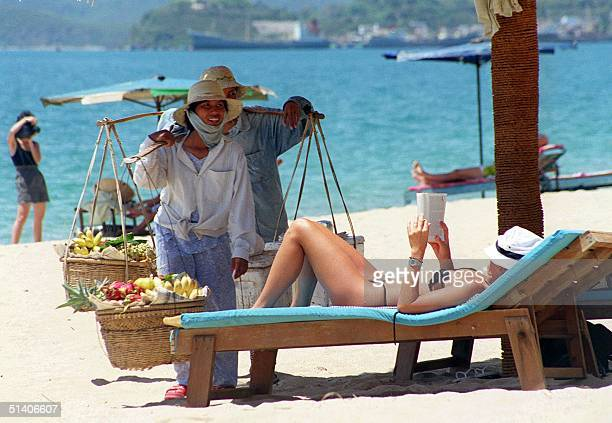 Fruit vendors approach a foreign tourist taking a sunbath on a beach in the central coastal city of Nha Trang 21 June According to official figures...