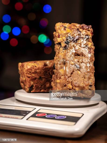 fruitcakes on kitchen scale with christmas lights in background - panyik-dale stock photos and pictures