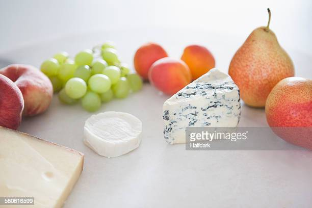 Fruits and cheese in plate against white background
