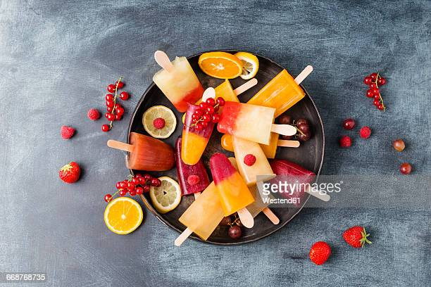 Fruits and different homemade ice lollies made of fruit juice and pulp