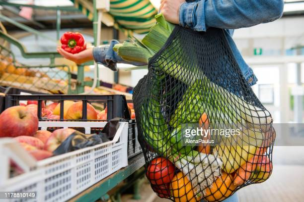 fruits and vegetables in a black cotton mesh reusable bag, zero waste shopping on outdoors market - mesh textile stock pictures, royalty-free photos & images