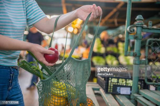 fruits and vegetables in a cotton mesh reusable bag, zero waste shopping on outdoors market - local produce stock pictures, royalty-free photos & images