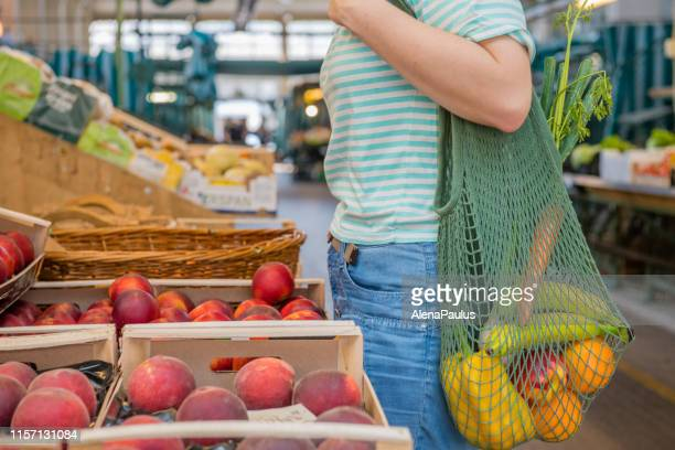 fruits and vegetables in a cotton mesh reusable bag, zero waste shopping concept - environmentalist stock pictures, royalty-free photos & images