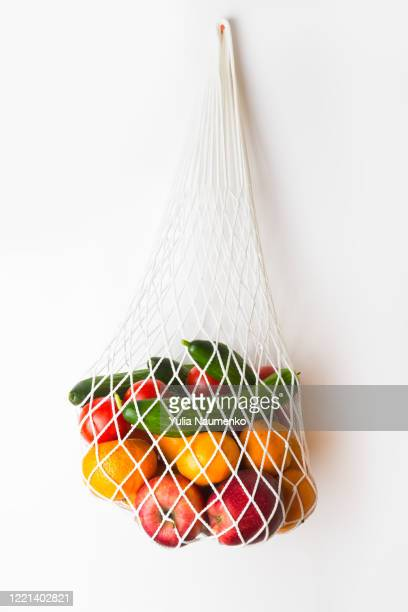 fruits and vegetables in a mesh bag. cucumbers and tomatoes and apples and oranges in a white ecological bag. eco zero waste concept, no plastic. - tessuto a rete foto e immagini stock