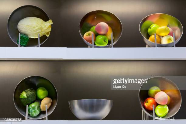 fruits and vegetables in bowls on the shelves - liyao xie stock pictures, royalty-free photos & images