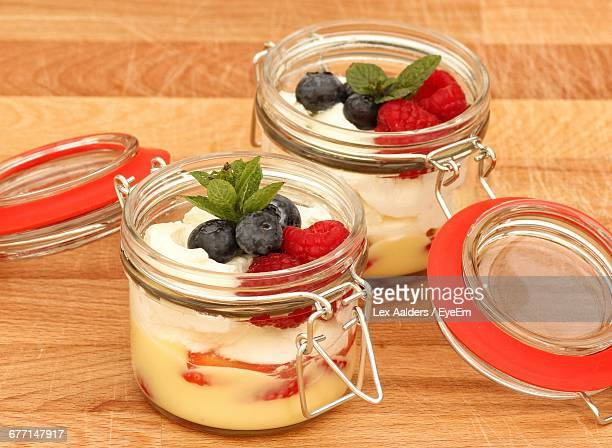 Fruits And Yogurts In Jars On Table