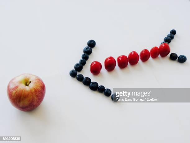 Fruits Arranged In Arrow Symbol Over White Background