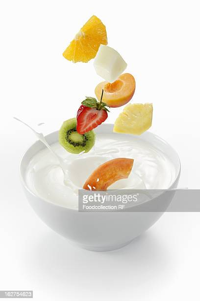 Fruits falling into bowl of yoghurt