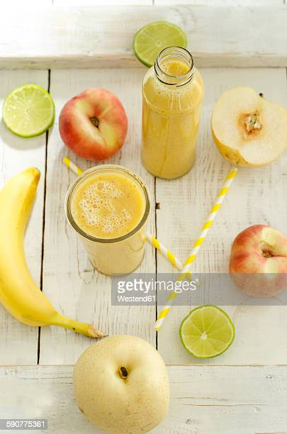 Fruits, glass bottle and glass of fruit smoothie on wood