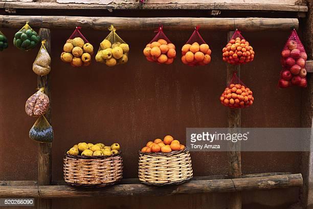 fruits hanging in baskets for sale - bancarella di verdura foto e immagini stock
