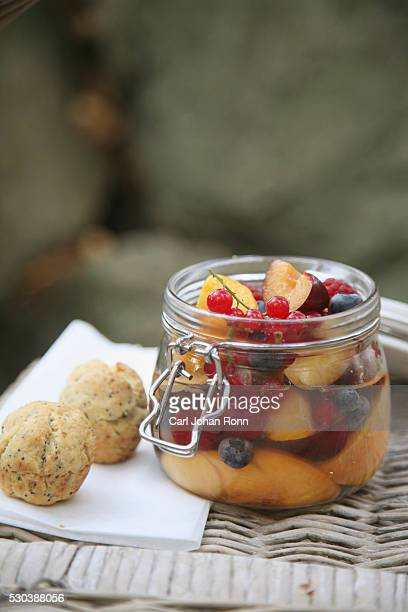 Fruits in glass jar, cakes on napkin