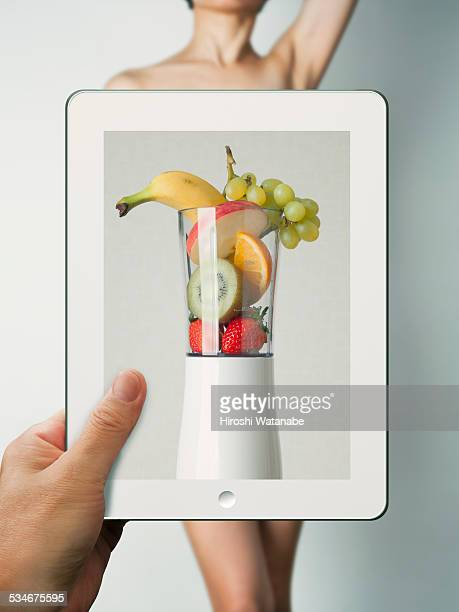 Fruits in mixer on tablet, and woman's body