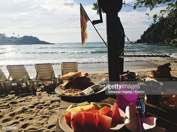 Fruits In Plate On Table At Beach Against Sky