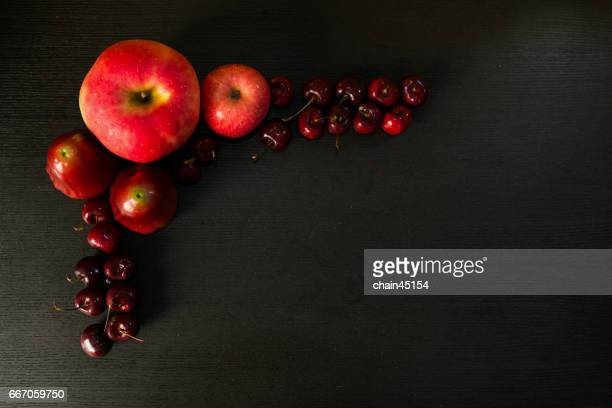 A fruits include apple, rose apple and cherry on a wood background.