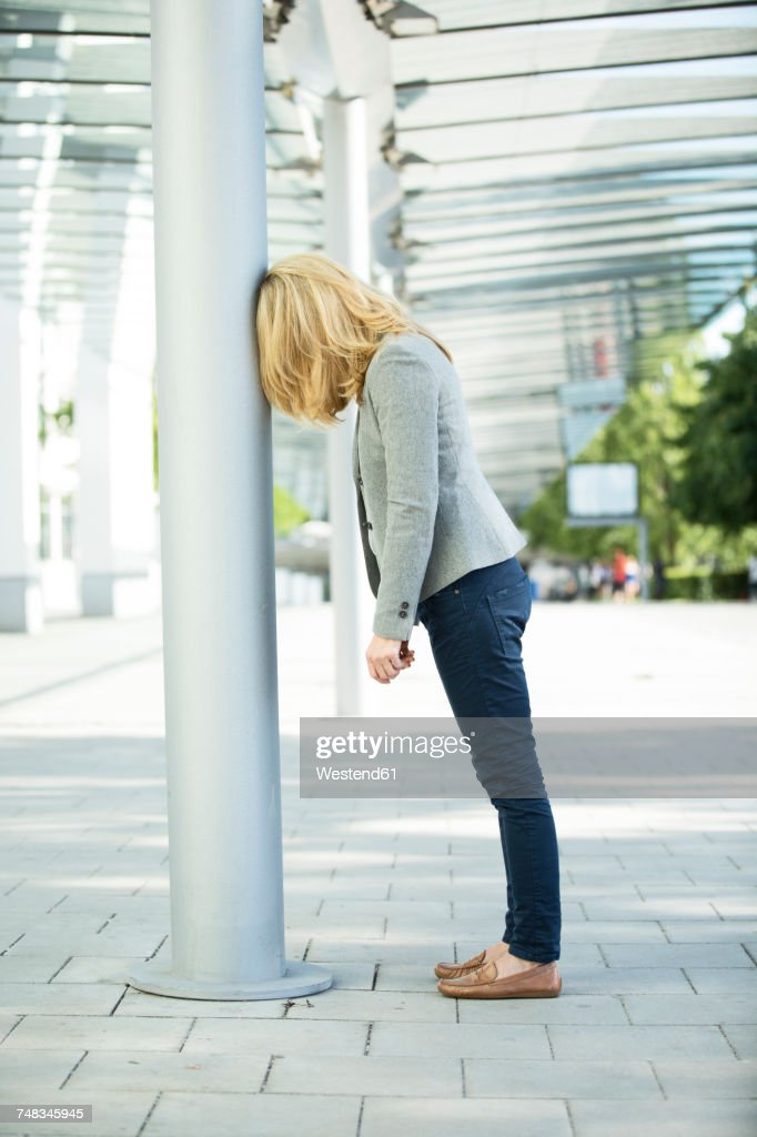 Frustated woman leaning against column : Foto de stock