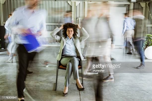 frustrated african american businesswoman surrounded by her colleagues in blurred motion. - anger stock pictures, royalty-free photos & images