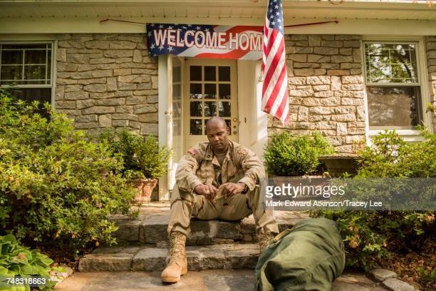 frustrated african american soldier sitting on front stoop - post traumatic stress disorder stock pictures, royalty-free photos & images