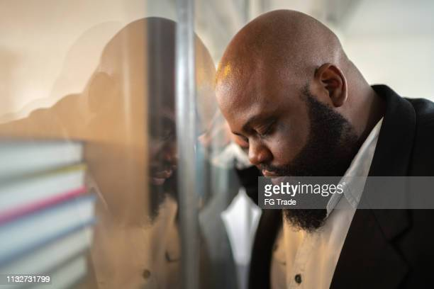 frustrated afro man feeling loser standing near the window - downsizing unemployment stock pictures, royalty-free photos & images
