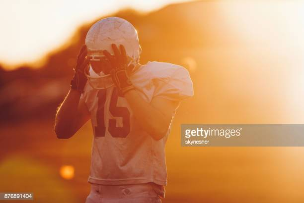 Frustrated American football player on the field at sunset.