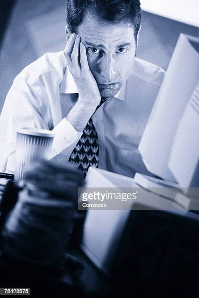 Frustrated and tired businessman working at computer