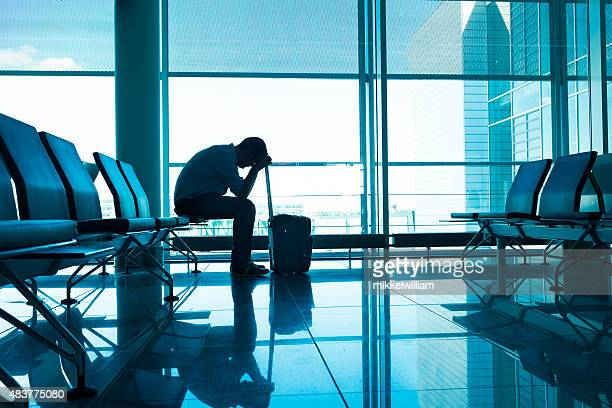 Frustrated and tired passenger waits for delayed plane at airport