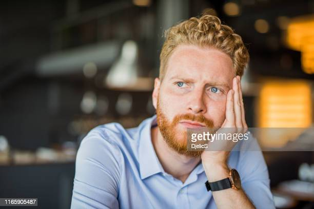 frustrated and worried young man contemplating alone in coffee shop. - uncertainty stock pictures, royalty-free photos & images