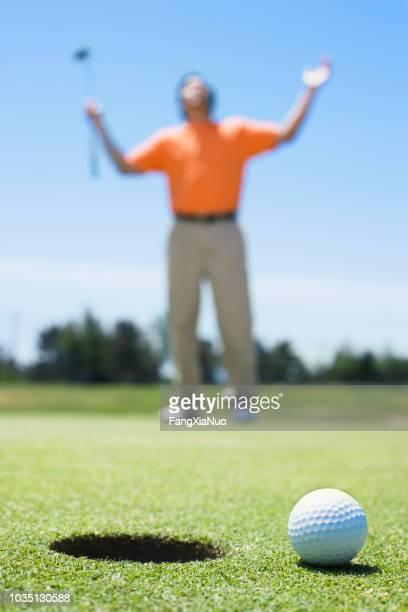 frustrerad asiatiska mannen på golfbana - puttning bildbanksfoton och bilder