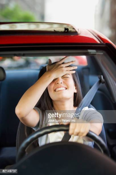 Frustrated Asian woman driving car