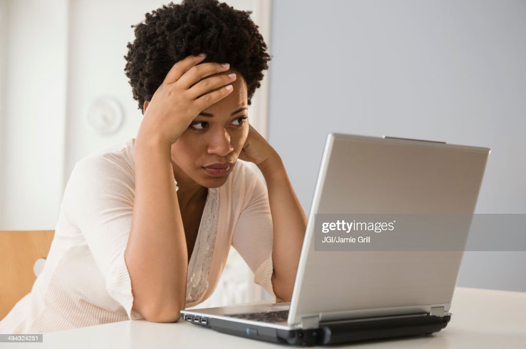 Frustrated Black businesswoman using laptop : Stock Photo