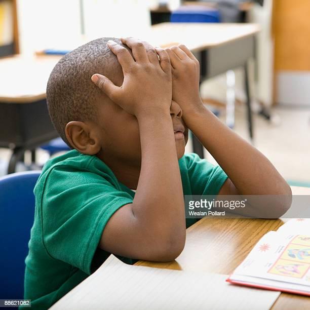 Frustrated boy rubbing eyes in classroom