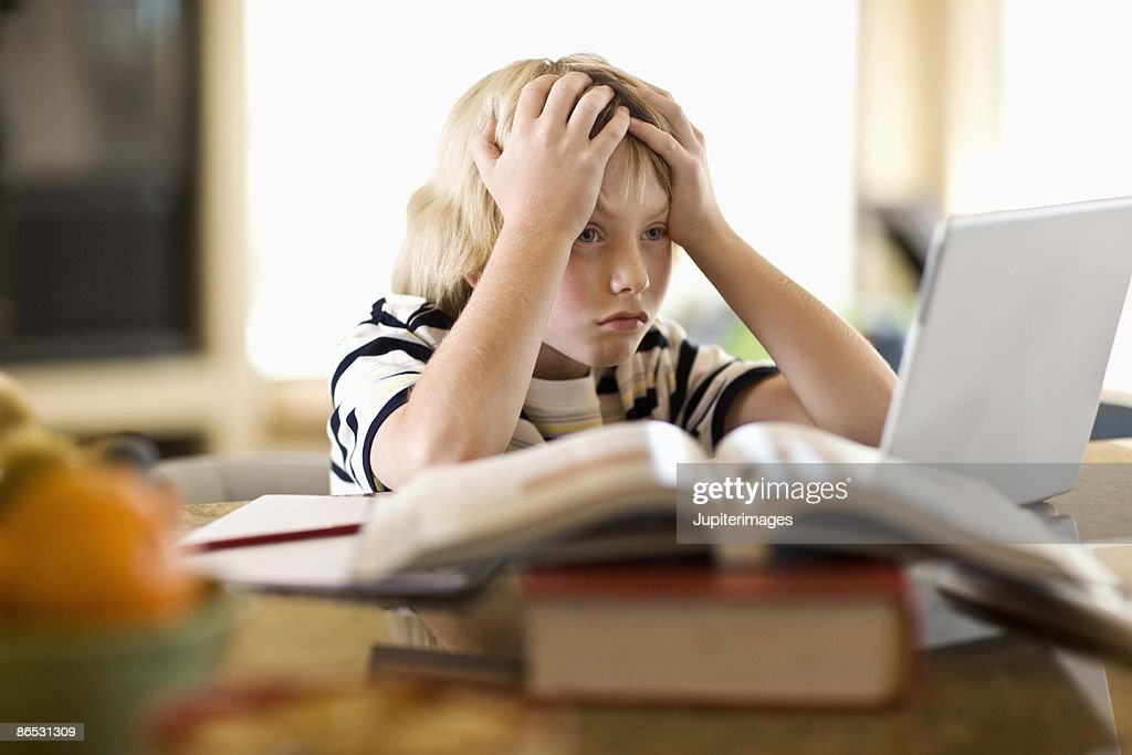Frustrated boy using laptop : Stock Photo