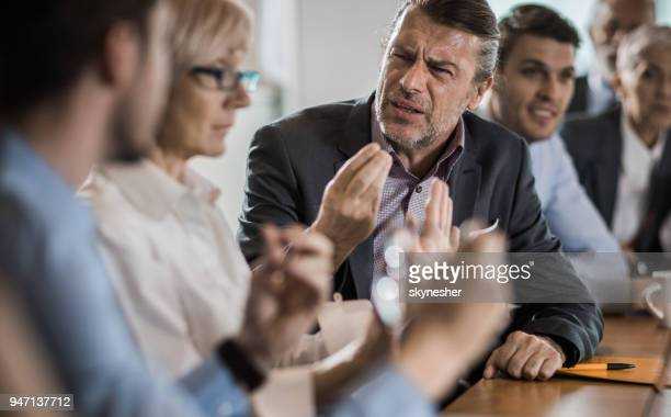 Frustrated businessman arguing with his colleague during a business meeting in the office.