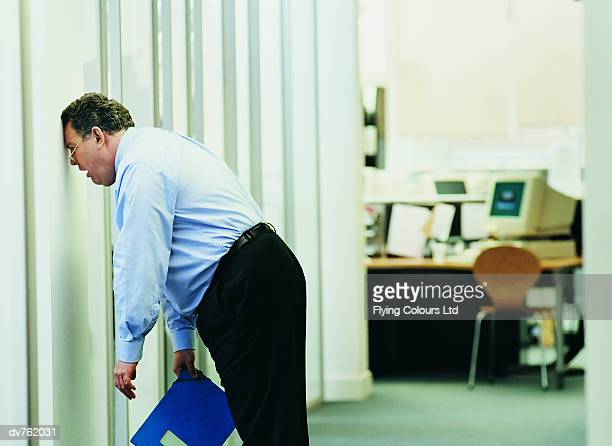 frustrated businessman banging his head against a brick wall in the office - frustratie stockfoto's en -beelden