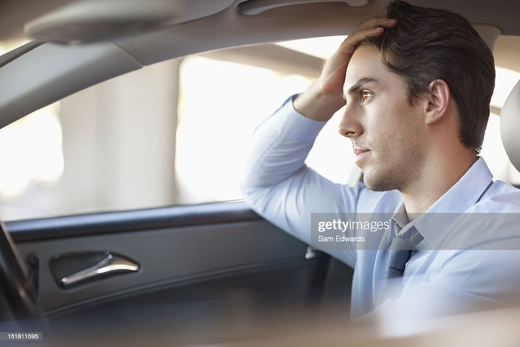 Frustrated businessman driving car : Stock Photo