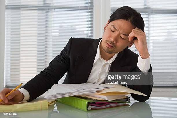 frustrated businessman in office - 手を顔にやる ストックフォトと画像