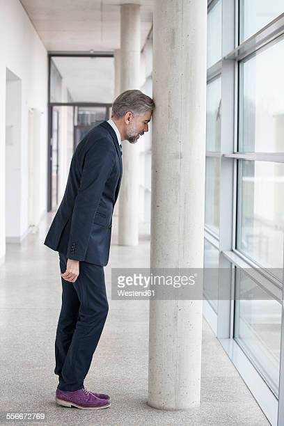 Frustrated businessman leaning against column