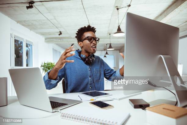 frustrated businessman looking at computer monitor - anger stock pictures, royalty-free photos & images