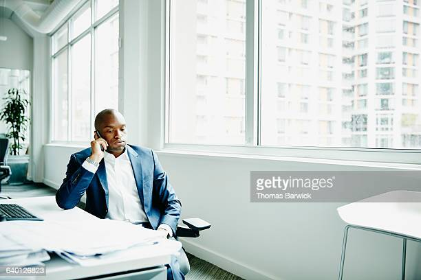 Frustrated businessman on smartphone in office