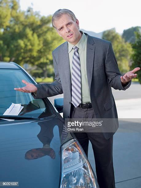 Frustrated businessman shrugging at parking ticket on windshield