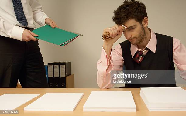 frustrated businessman sitting at desk full of documents colleague giving him file - delegating stock photos and pictures