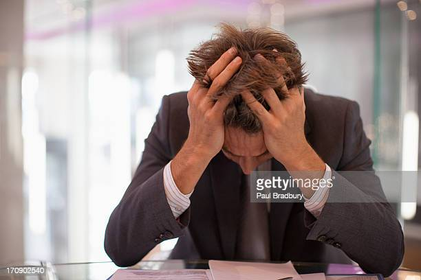 frustrated businessman sitting at desk with  head in hands - head in hands stock pictures, royalty-free photos & images