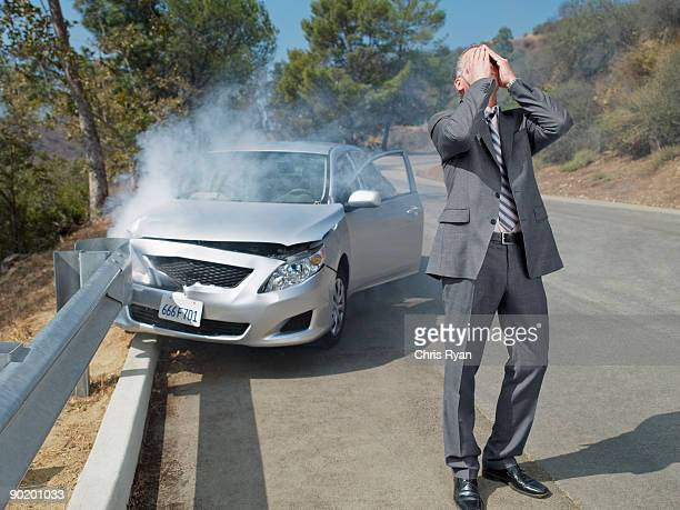 frustrated businessman standing next to car wrecked on guardrail - crash stock pictures, royalty-free photos & images