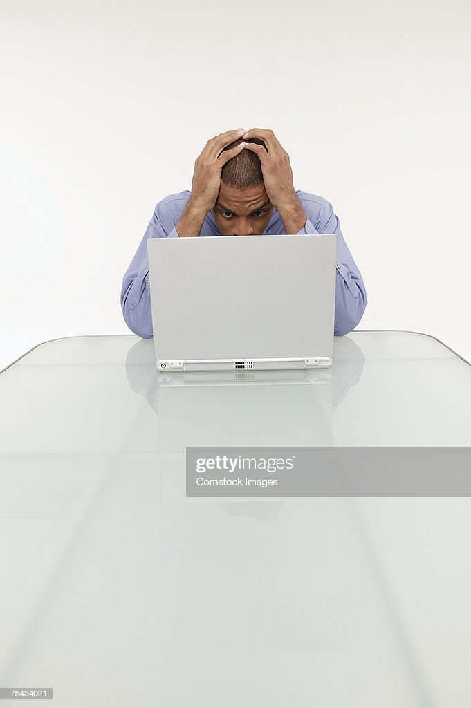 Frustrated businessman using a laptop : Stockfoto