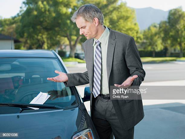 frustrated businessman viewing parking ticket on windshield - ticket stock pictures, royalty-free photos & images