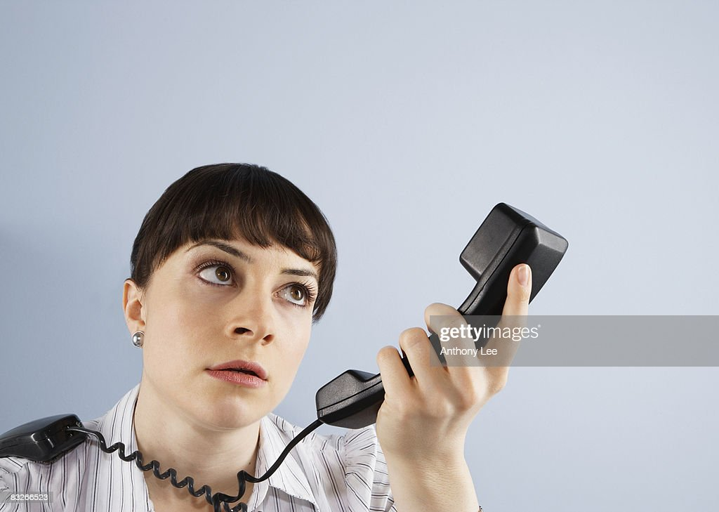 Frustrated businesswoman looking at telephone handset : Stock Photo