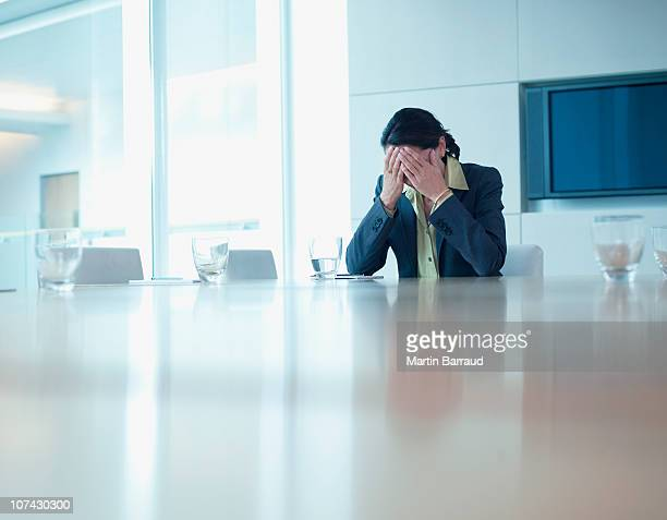 frustrated businesswoman sitting at conference table - head in hands stock pictures, royalty-free photos & images